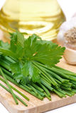 Chives, parsley, garlic and olive oil on a wooden board, closeup Royalty Free Stock Photos