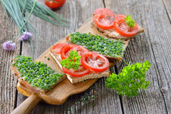 Chives and tomato snack. Vegetarian snack: Slices of buttered farmhouse bread with fresh chives and tomatoes on a wooden board Stock Photography