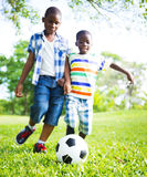 Chldren playing football Focus on the ball Stock Photos