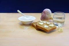 Chleb, czosnek, sól, ajerówka na stole fotografia stock