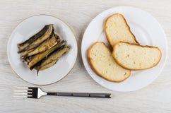 Chleb, konserwować brzdąc w talerzu, rozwidlenie na drewnianym stole obraz royalty free