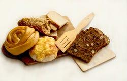 Chleb, rolki i ciasta na tnącej desce, obrazy stock