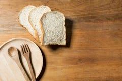 Chleb z drewnianym talerzem na drewnianym odgórnym widoku Zdjęcia Stock