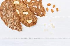 Chleb z flaxseeds i migdałami na białym drewnianym tle Pożytecznie żywienioniowy surowy chlebowy weganinu śniadanie bez drożdże obrazy stock