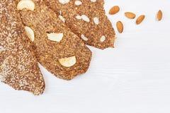 Chleb z flaxseeds i migdałami na białym drewnianym tle Pożytecznie żywienioniowy surowy chlebowy weganinu śniadanie bez drożdże obrazy royalty free
