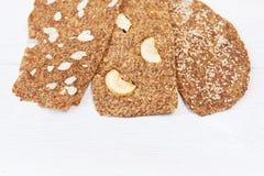 Chleb z flaxseeds i migdałami na białym drewnianym tle Pożytecznie żywienioniowy surowy chlebowy weganinu śniadanie bez drożdże zdjęcia stock