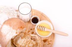 Chleb z miodem, mlekiem na drewnie i białym tłem, Obraz Royalty Free
