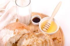 Chleb z miodem, mlekiem na drewnie i białym tłem, Zdjęcia Royalty Free