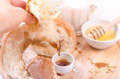 Chleb z miodem, mlekiem na drewnie i białym tłem, Obrazy Stock