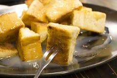 Chlebowa grzanka z masłem i kondensującym mlekiem w talerzu, wybrana ostrość Zdjęcia Royalty Free