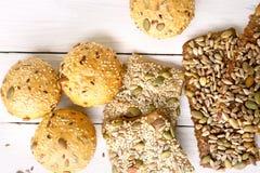 Chlebowe babeczki z różnorodnymi ziarnami na białym drewnianym stole Zdjęcia Stock