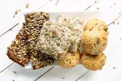 Chlebowe babeczki z różnorodnymi ziarnami na białym drewnianym stole Obrazy Stock