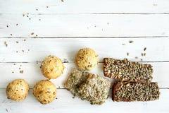 Chlebowe babeczki z różnorodnymi ziarnami na białym drewnianym stole Obraz Royalty Free