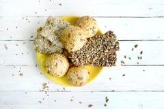 Chlebowe babeczki z różnorodnymi ziarnami w koloru żółtego talerzu na białym drewnianym stole Fotografia Stock