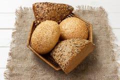 Chlebowe rolki w koszu na nieociosanym drewnianym tle zdjęcia royalty free