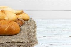 Chlebowi baguettes na nieociosany biel malującym drewnie zdjęcia stock