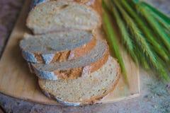 Chlebowy plasterek na drewnianej desce Pszeniczny świeży bochenek Zdjęcie Stock