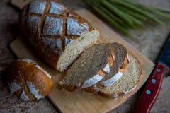 Chlebowy plasterek na drewnianej desce Pszeniczny świeży bochenek Fotografia Royalty Free