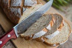 Chlebowy plasterek na drewnianej desce Pszeniczny świeży bochenek Zdjęcia Stock
