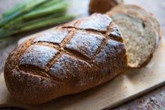 Chlebowy plasterek na drewnianej desce Pszeniczny świeży bochenek Fotografia Stock