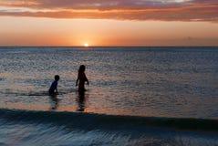 Chlidren die in oceaangolven bij zonsondergang waden Royalty-vrije Stock Foto's