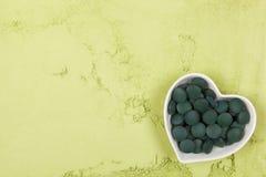 Chlorella and spirulina background. Spirulina; chlorella and wheatgrass. Green food supplement. Green pills and ground powder. Healthy lifestyle Stock Image