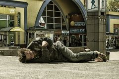 Chmielny bezdomny mężczyzna śpi na betonie w szerokim świetle dziennym zdjęcia stock