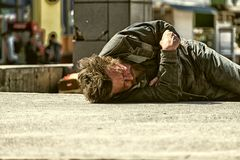 Chmielny bezdomny mężczyzna śpi na betonie w szerokim świetle dziennym obraz stock