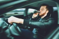 Chmielny mężczyzna jedzie samochód z butelką alkohol w jego ręce Obsługuje whisky od żelaznej kolby za kołem samochód fotografia royalty free
