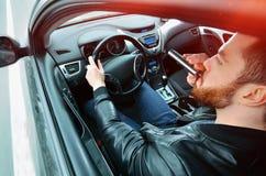 Chmielny mężczyzna jedzie samochód z butelką alkohol w jego ręce Obsługuje whisky od żelaznej kolby za kołem samochód obrazy stock
