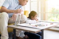 Chmielny ojciec uczy twój dziecka robić pracie domowej i córki płacze w domu, Rodzinni zagadnienia zdjęcie stock