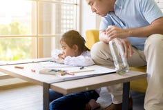 Chmielny ojciec uczy twój dziecka robić pracy domowej i córki płaczowi, Ogólnospołeczni rodzinni zagadnienia obrazy royalty free