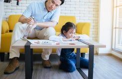 Chmielny ojciec uczy twój dziecka robić pracy domowej i córki płaczowi, Rodzinni zagadnienia zdjęcia royalty free