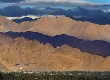 Chmurna pogoda w górach: błękitne burz chmury ciskać ocieniają na szykach, część wzgórza zaświecają słońcem, część są ciemne, Obrazy Stock