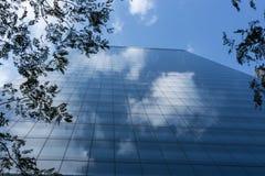 Chmurnego niebieskiego nieba odbicia drapacza chmur drzew szklany zewnętrzny frami zdjęcia royalty free