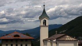 Chmurnieje timelapse na górach z małym wiejskim kościół zbiory
