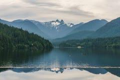 Chmurny dzień na halnym jeziorze i zieleń lesie Obraz Royalty Free