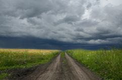 Chmurny lato krajobraz z zmieloną wiejską drogą zdjęcia stock