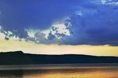 Chmurny niebo i duży jezioro blisko gór Zdjęcia Royalty Free