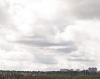 Chmurny niebo nad miasta tłem chmurzący niebo Obraz Stock