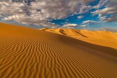 Chmurny niebo nad piasek diunami w pustyni obraz royalty free