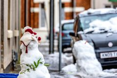 Chmurny zima dnia widok domowej roboty bałwan na typowym brytyjskim drogowym footpath obok pustych przetwarza koszy pudełek Fotografia Royalty Free