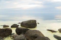 Chmurny zmierzch i spokojny jezioro z skałami w przedpolu obraz royalty free