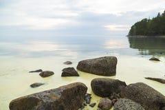 Chmurny zmierzch i spokojny jezioro z skałami w przedpolu i drzewie zdjęcie royalty free