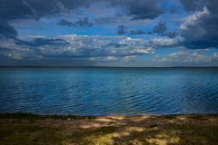 Chmury i słońce promienie nad jeziorem przy wschodem słońca zdjęcie royalty free