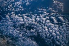 Chmury na niebieskim niebie, odgórny widok od okno samolot fotografia royalty free
