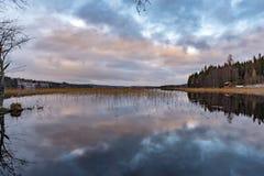 Chmury odbijali mnie wewnątrz uspokajają jezioro w Szwecja fotografia stock