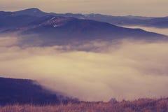Chmury unoszą się wśród wzgórzy w zim górach Obraz Stock