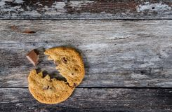 Choc chip cookie made to look like a popular arcade character, eating a chocolate chunk. This large, home baked cookie is seen on a rustic wooden table, having Royalty Free Stock Photography