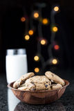 Choc Chip Cookies and Milk. Chocolate chip cookies and milk on a granite table with lights on the background Royalty Free Stock Photo